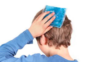 young boy holding a blue ice pack to his head