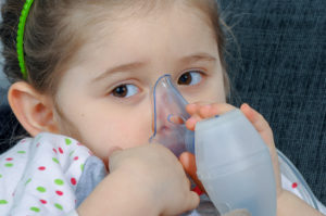Little girl holding inhaler mask.