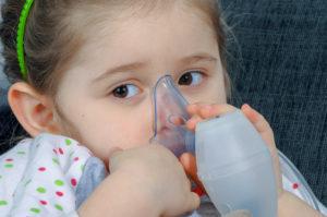 Little girl holding inhaler mask.